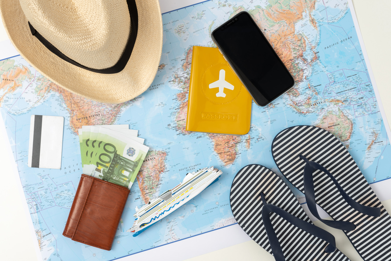 A flat lay picture of all the necessary things for a modern summer trip, including a credit card, summer accessories and a smartphone