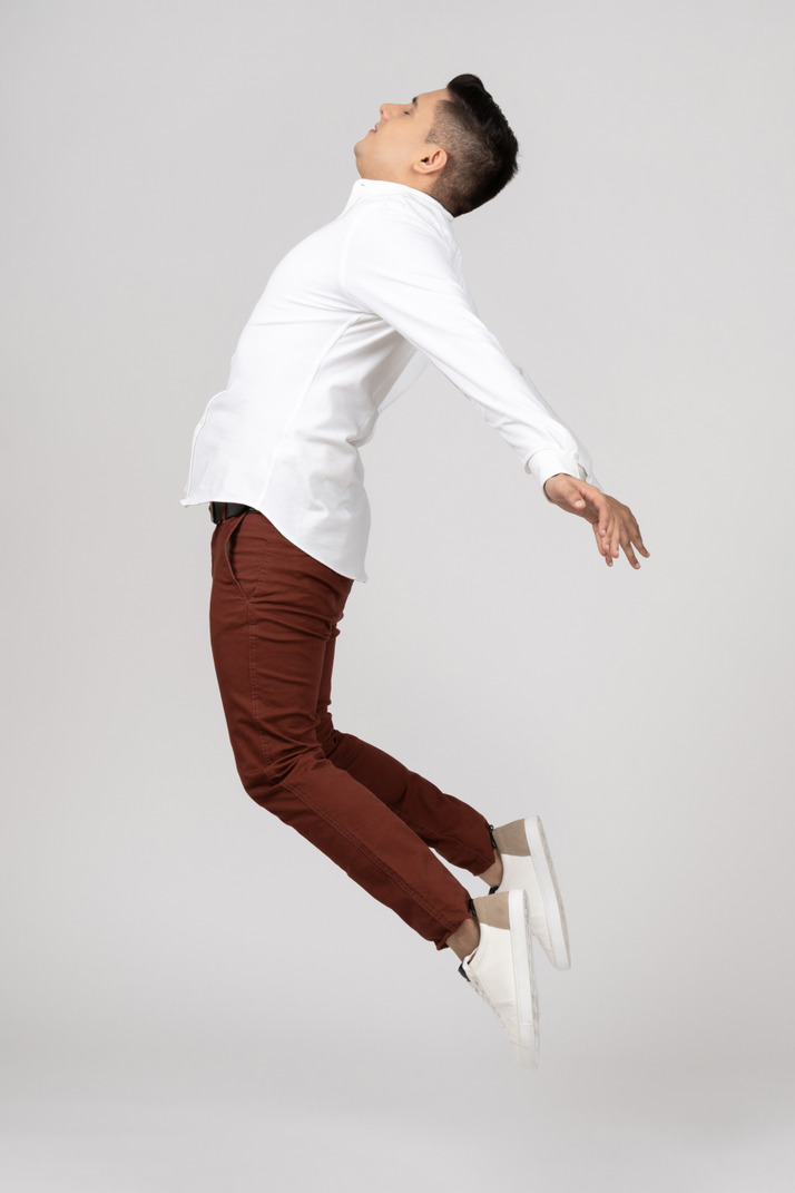Side view of a young latino man stretching in the air