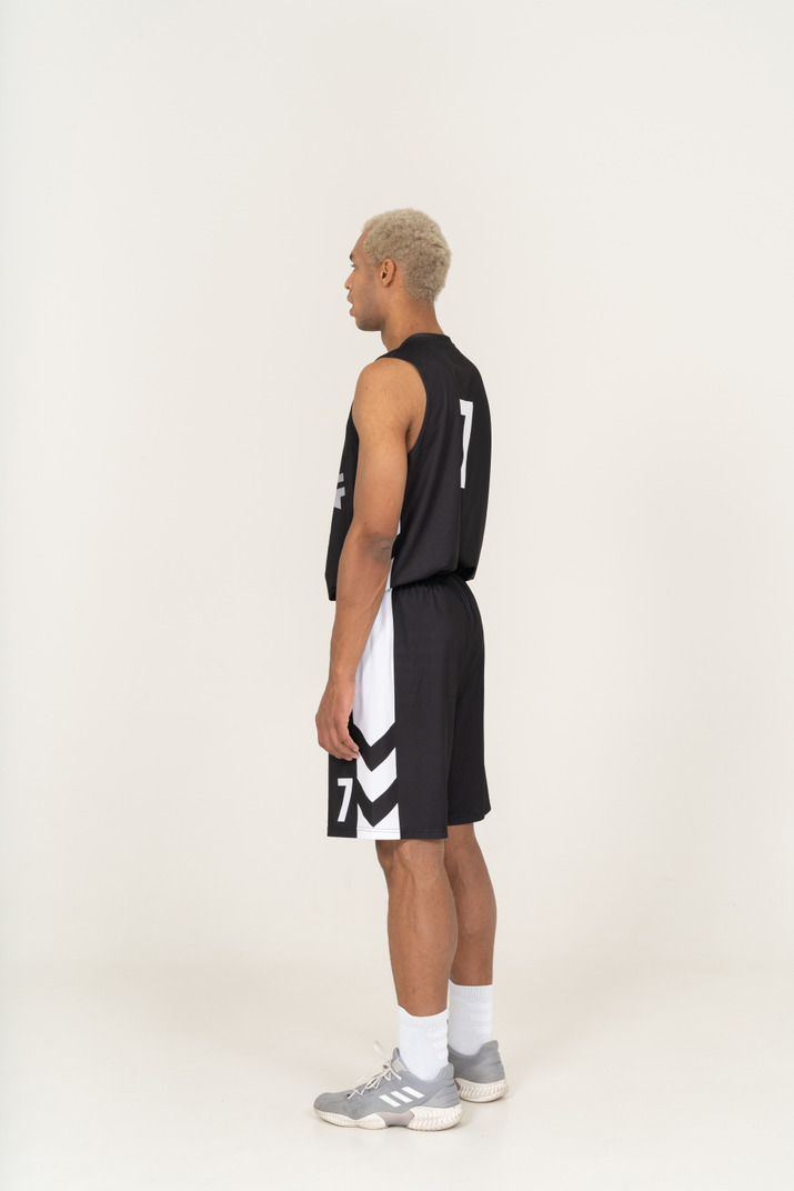 Three-quarter back view of a gasping young male basketball player
