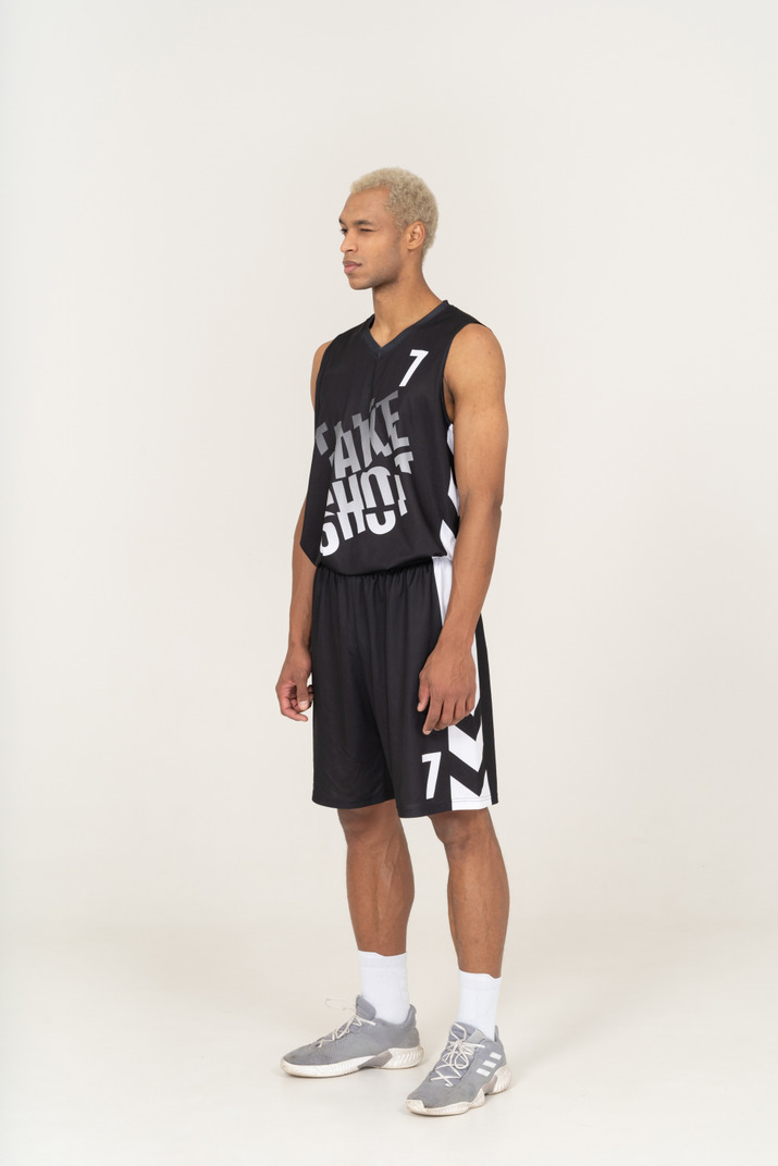 Three-quarter view of a young male basketball player standing with one eye open