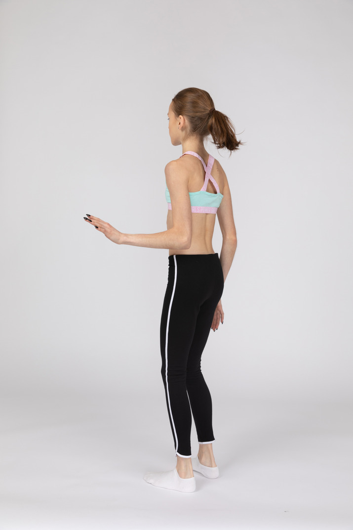 Dreiviertel-rückansicht eines jugendlichen mädchens in der sportbekleidung, die still steht und hand hebt