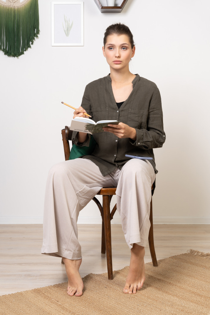 Front view of a thoughtful young woman wearing home clothes sitting on a chair with pencil and notebook