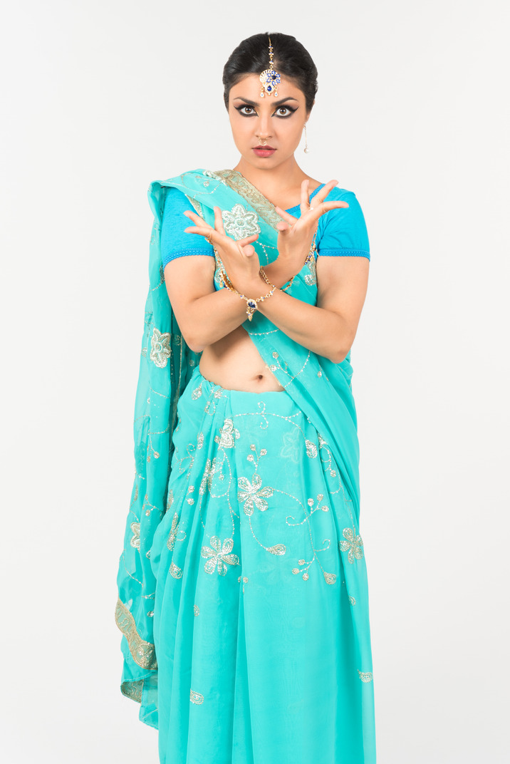 Young indian woman in blue sari standing in dance position