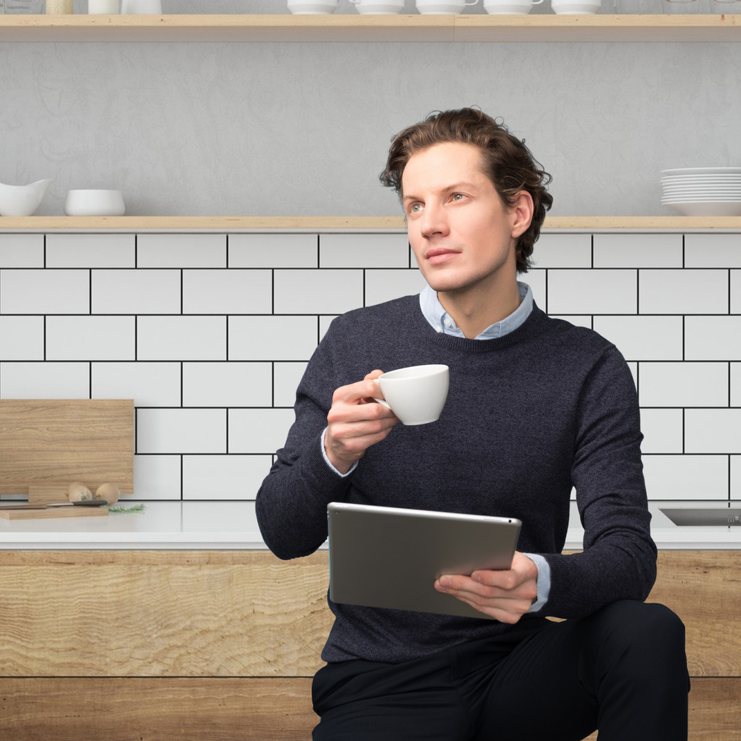 Dreamy handsome guy holding a cup and a laptop in his hands