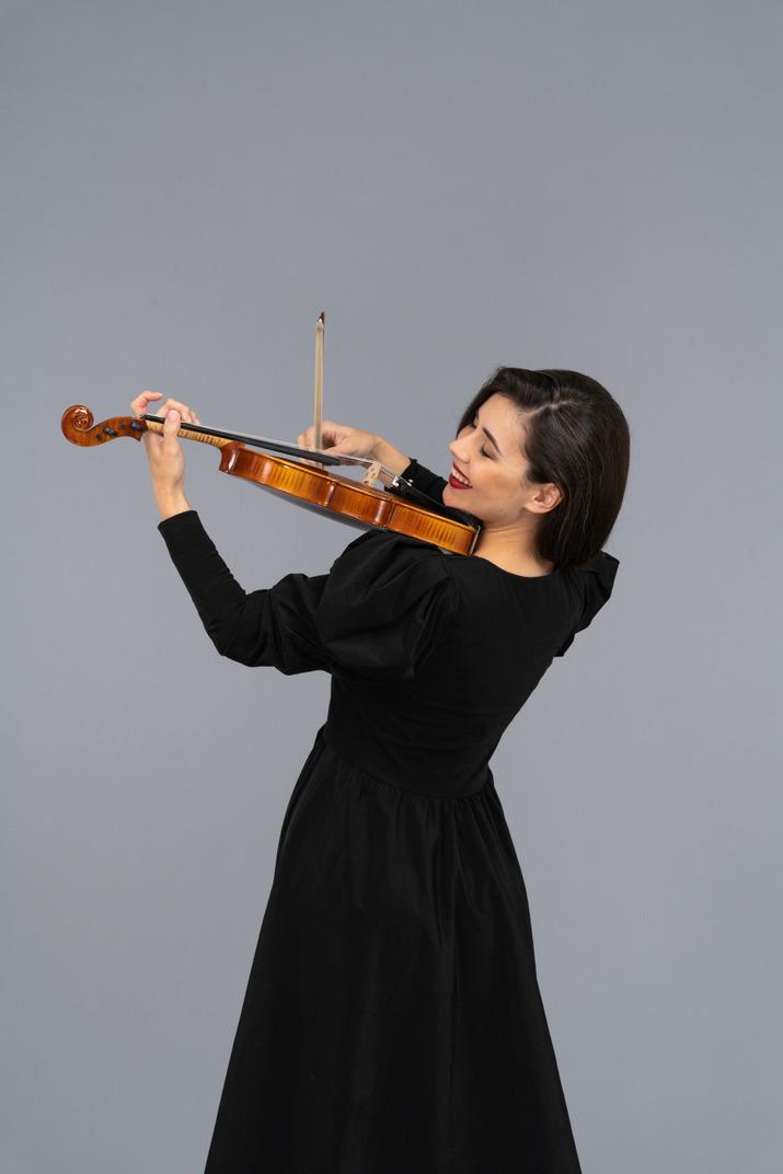 バイオリンを弾く黒いドレスを着た若い陽気な女性のクローズアップ