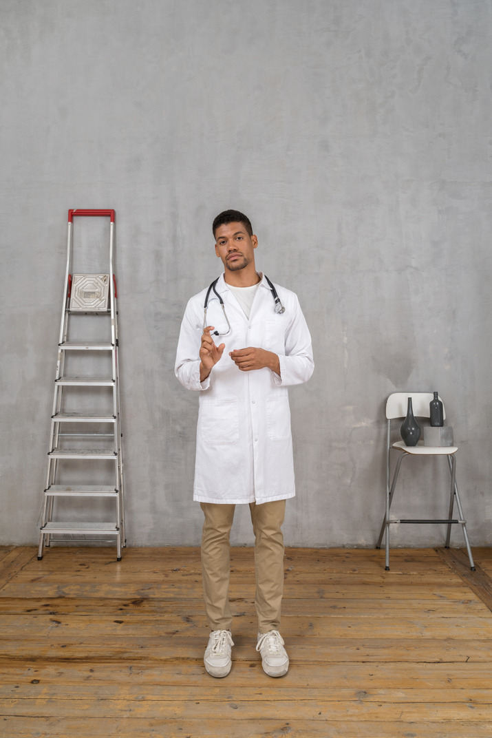 Front view of a young doctor standing in a room with ladder and chair showing a size of something