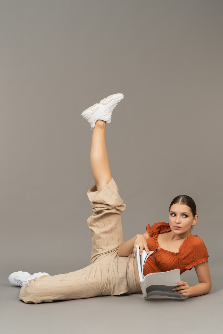 Young woman stretching her leg while holding a book