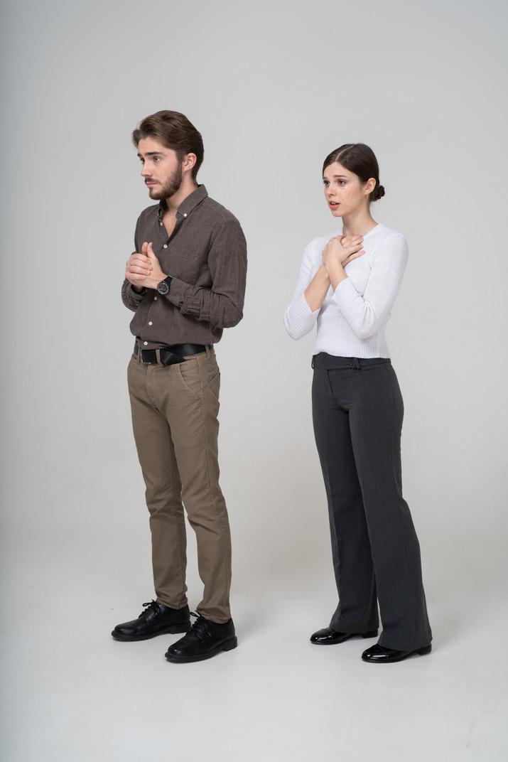 Dreiviertelansicht eines besorgten jungen paares in bürokleidung, das händchen hält