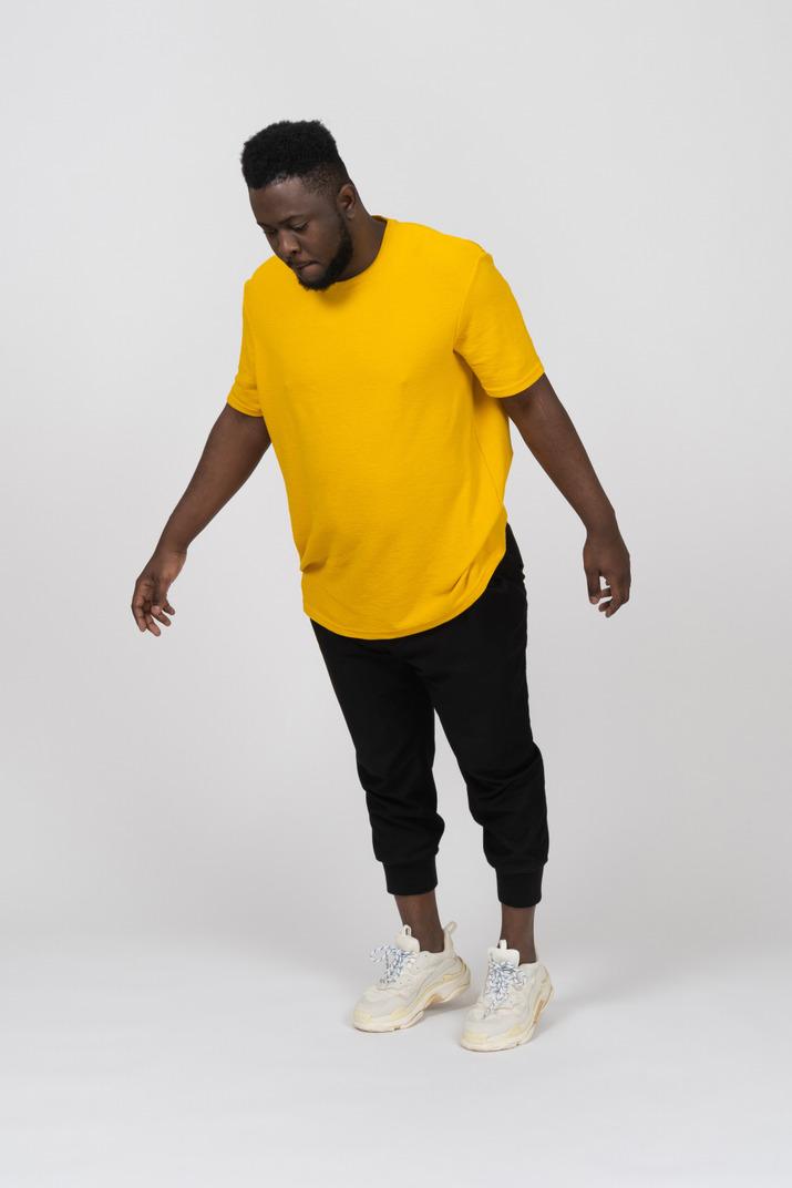 Vue de trois quarts d'un jeune homme à la peau foncée en t-shirt jaune se penchant en avant et étendant le bras