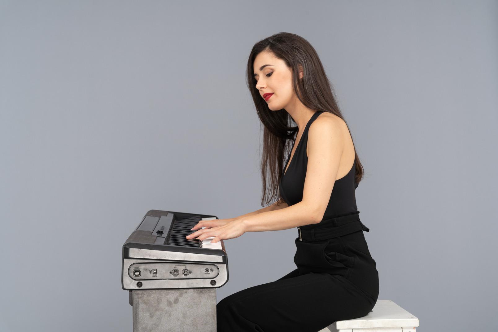 Vista lateral, de, un, señorita, en, traje negro, sentado, y, tocar el piano