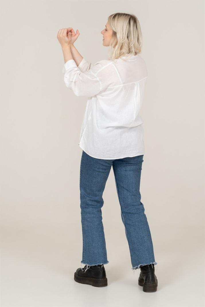 Dreiviertel-rückansicht einer blonden frau in freizeitkleidung, die hände hebt und eine herzgeste zeigt