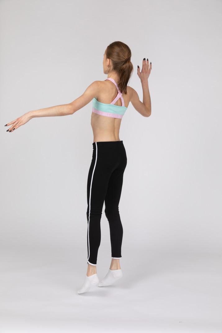 Dreiviertel-rückansicht eines jugendlichen mädchens in der sportbekleidung, die hand hebt und springt