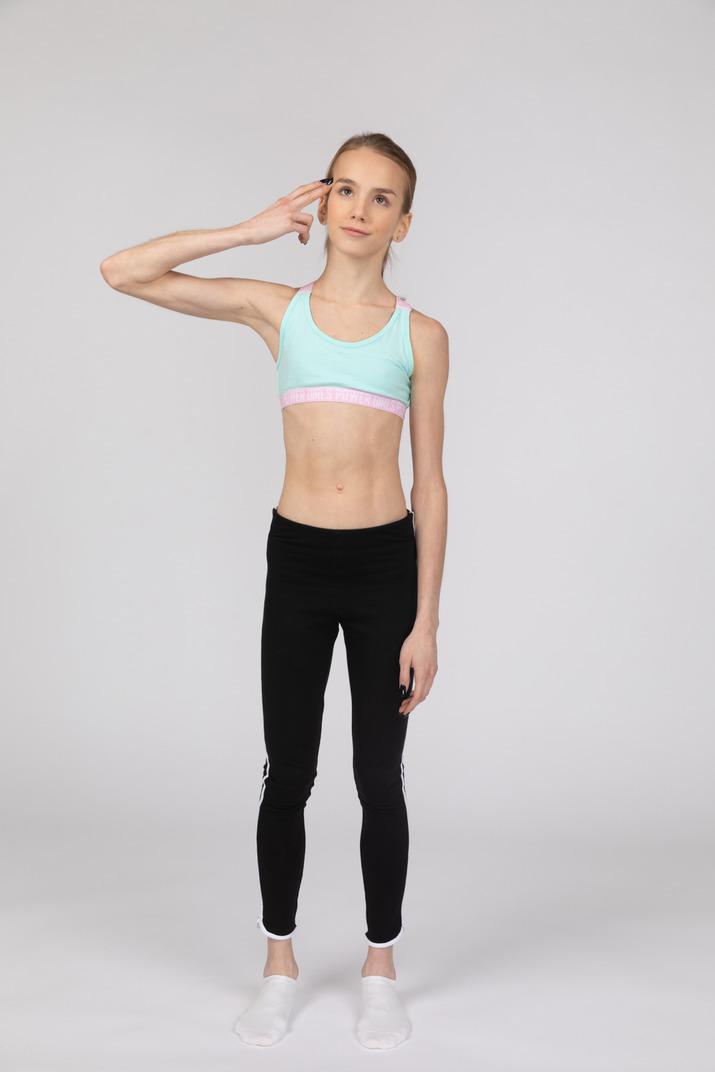 Vorderansicht eines jugendlich mädchens in der sportbekleidung, die kopf berührt