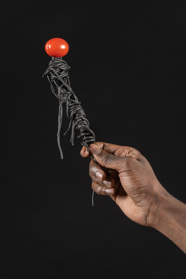 チェリー トマトの黒いパスタを持つ人間の手のクローズ アップ