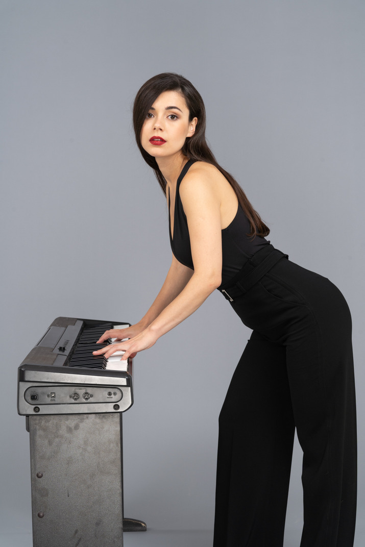 Side view of a young lady in black suit playing the piano while raising head while looking at camera