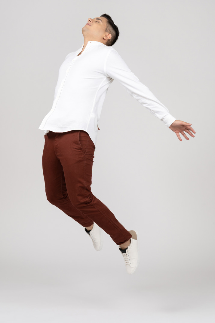 Three-quarter view of a young latino man stretching in the air