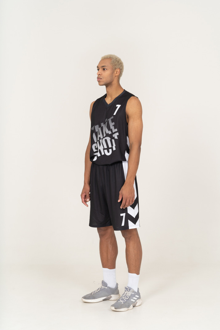 Three-quarter view of a young male basketball player standing still