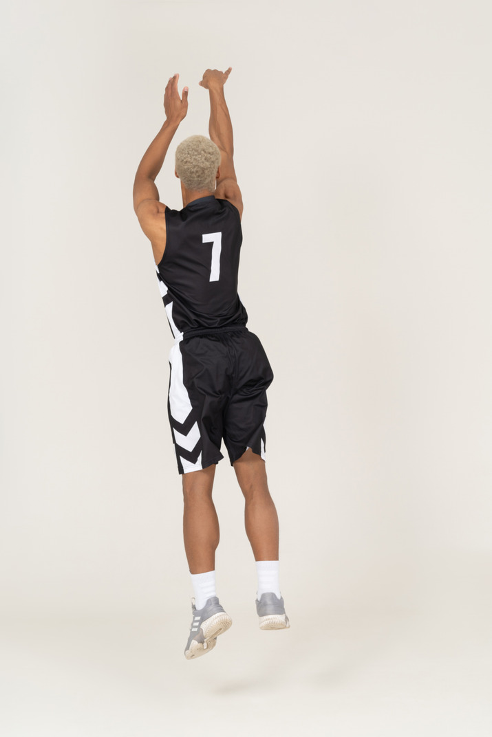 Three-quarter back view of a young male basketball player throwing something
