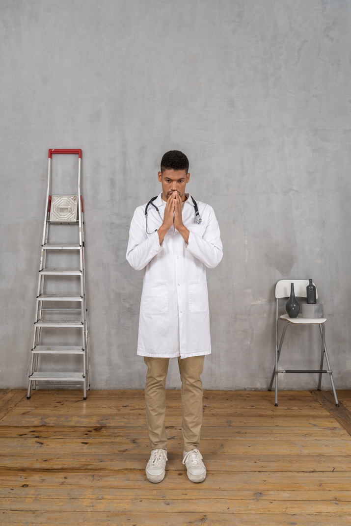 Front view of a worried young doctor standing in a room with ladder and chair