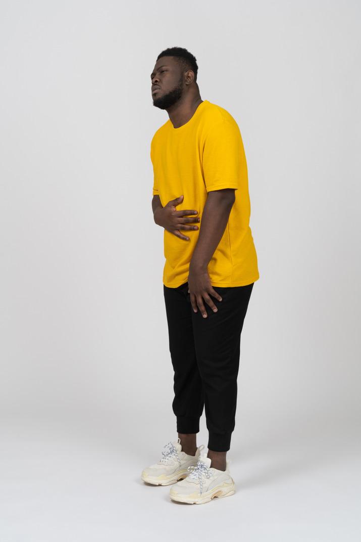 Vue de trois quarts d'un jeune homme à la peau foncée en t-shirt jaune touchant l'estomac