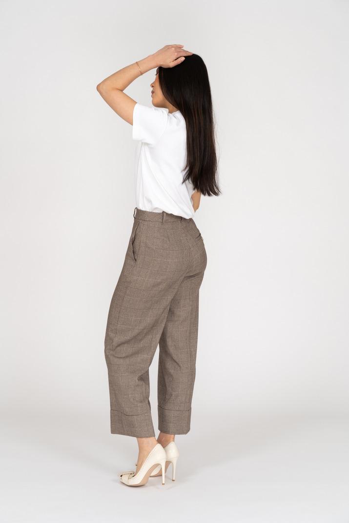 Seitenansicht einer jungen dame in reithose und t-shirt, die ihren kopf berührt