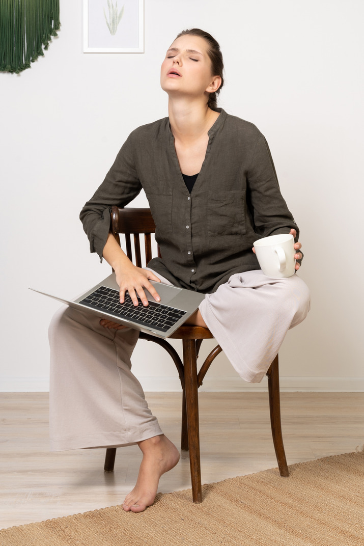 Front view of a tired young woman wearing home clothes sitting on a chair with a laptop & coffee cup