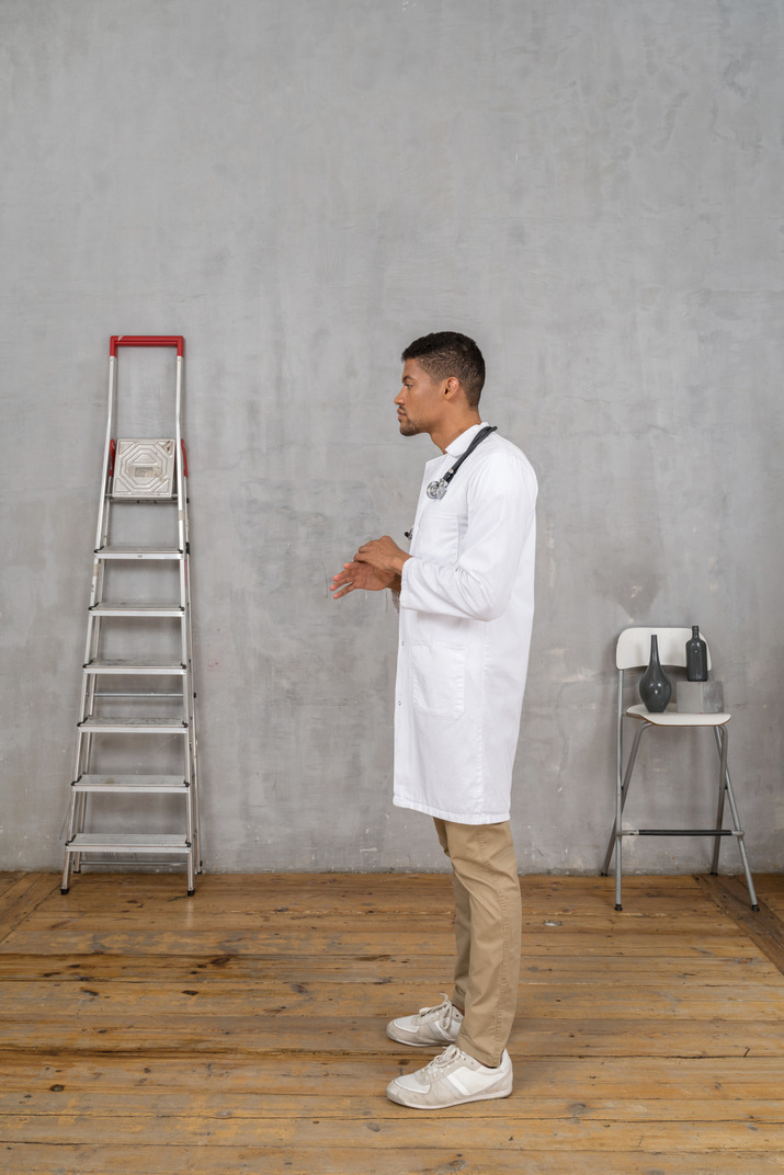 Side view of a gesticulating young doctor standing in a room with ladder and chair