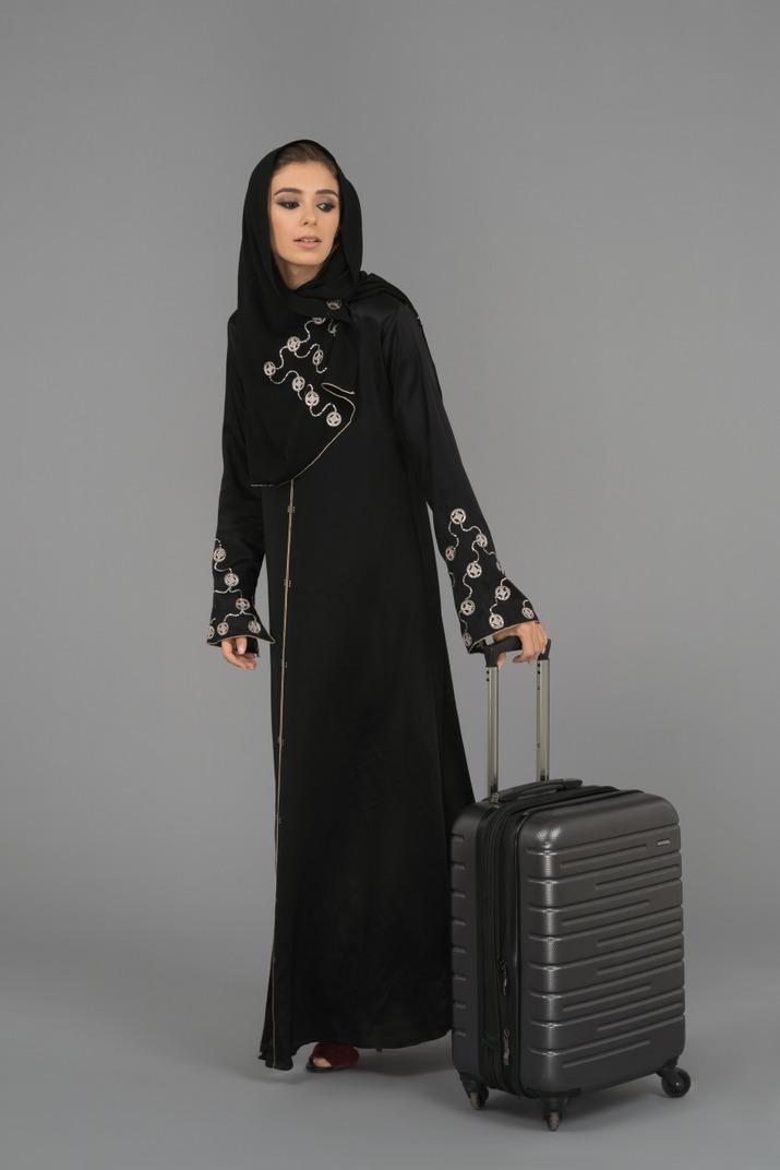 Eine bedeckte muslimische frau, die mit einer gepäcktasche steht
