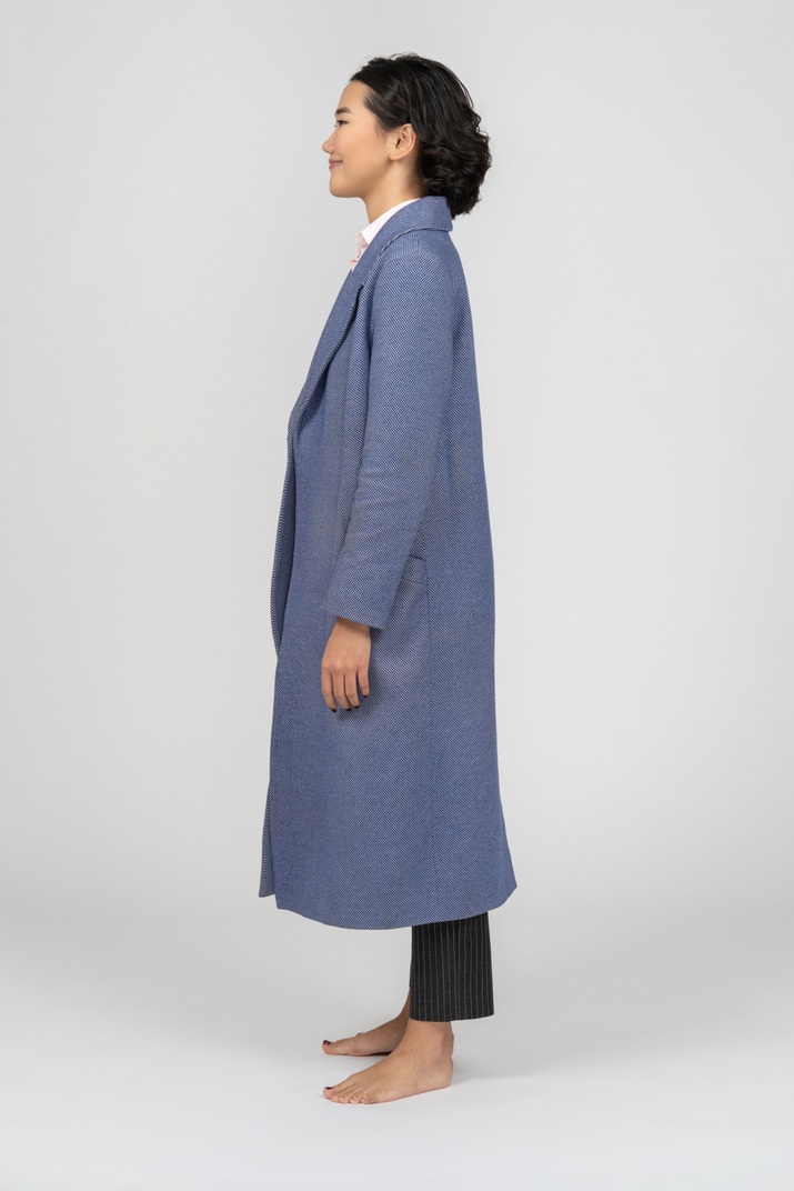Young woman in long blue coat standing in profile