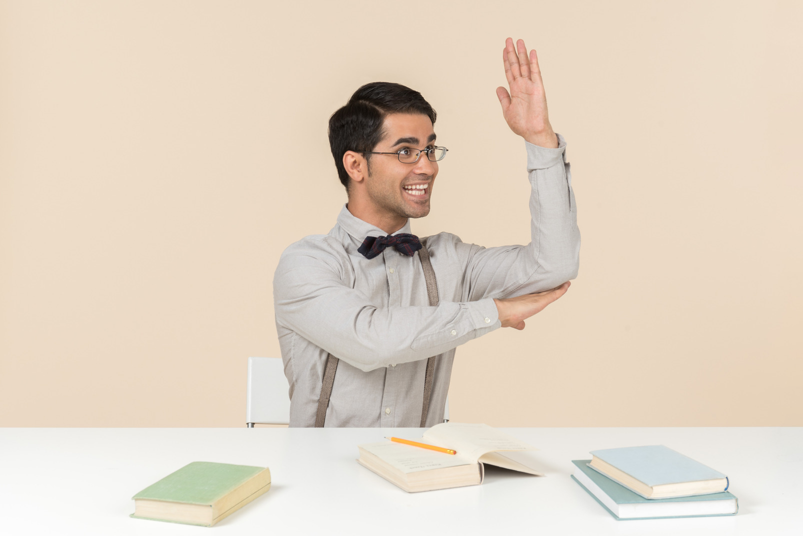 Adult student sitting at the table and raising a hand