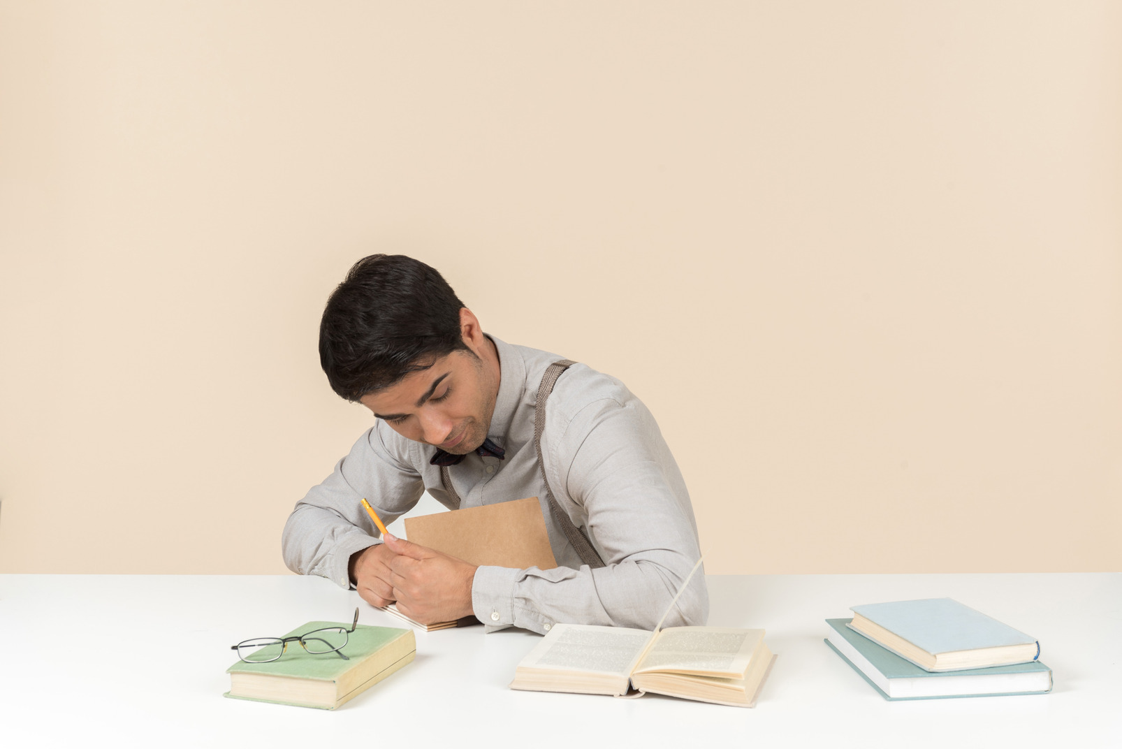 Young adult student sitting at the table and writing something down in the book