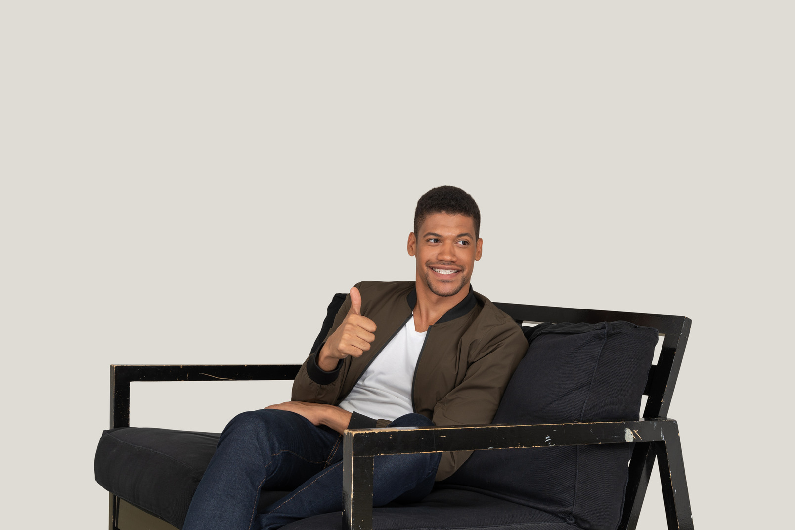 Smiling young man sitting on the sofa and showing thumb up