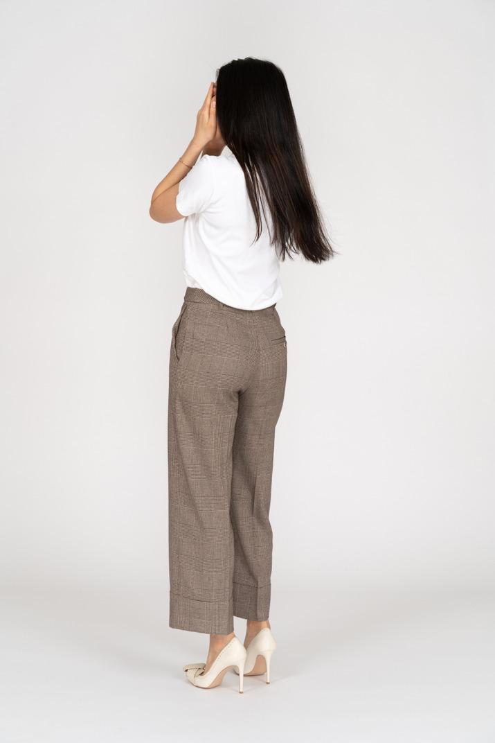 Dreiviertel-rückansicht einer jungen dame in reithose und t-shirt, die ihr gesicht versteckt