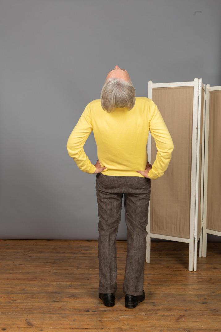 Rückansicht eines alten mannes, der hände auf die hüften legt, während er sich zurücklehnt